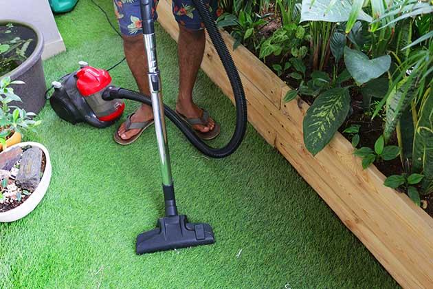 Pessoa sabe como limpar grama sintética com aspirador de pó