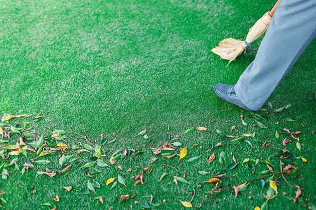 Pessoa sabe como limpar grama sintética varrendo o chão