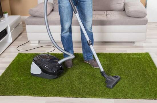 Homem sabe como limpar grama sintética com aspirador e tapete