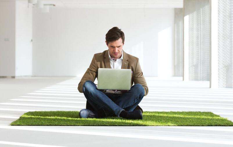 Homem sentado em cima do tapete tipo grama: saiba como escolher tapete
