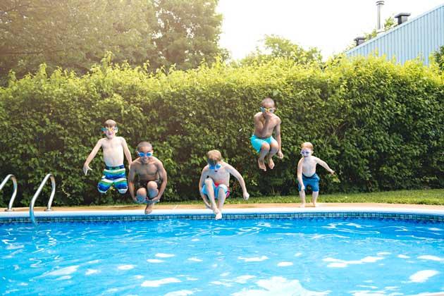 crianças brincando na grama sintética ao redor da piscina