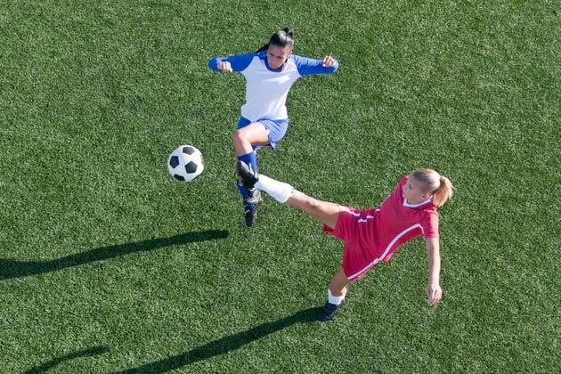 mulheres disputando bola numa partida de futebol