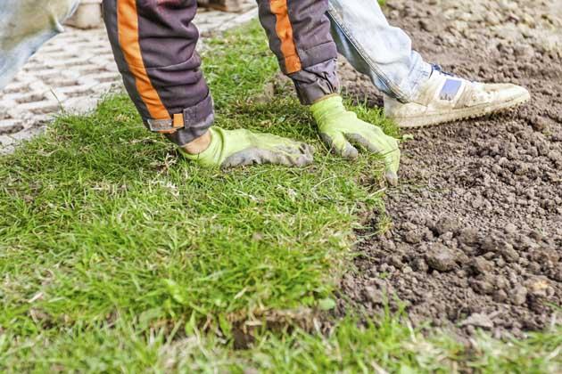 Pessoa com luvas fazendo a instalação de grama sintética na terra