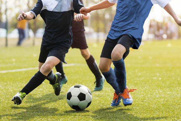 Três jogadores de futebol jogando sobre a grama padrão FIFA