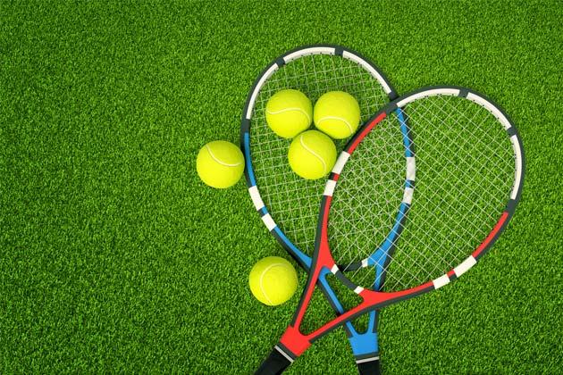 raquetes e bolas na grama sintética na quadra de tênis
