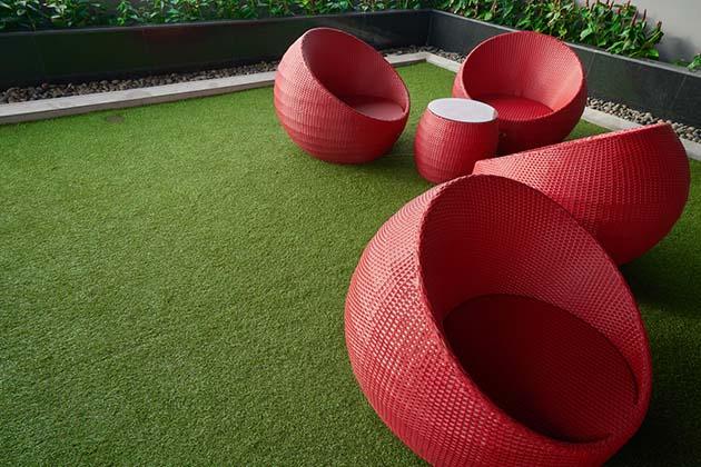 Grama sintética para reformar o piso e poltronas vermelhas