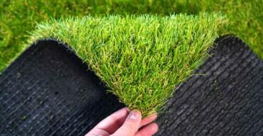 Mão analisando um tapete artificial antes de comprar grama sintética