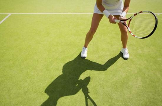 Mulher jogando tênis em quadra que contém grama sintética no piso para quadra de tênis