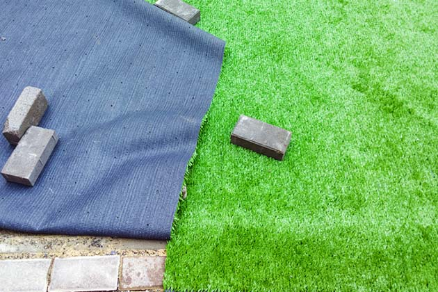 grama sintética no piso de cimento com tijolos