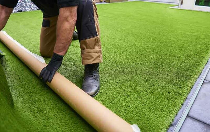 Profissional desenrola tapete artificial e instala grama sintética no piso de cimento