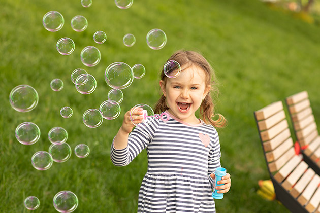 menina brincando com bolha de sabão aproveitando as vantagens da grama sintética para crianças