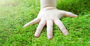 criança com a mão no chão simulando as vantagens da grama sintética
