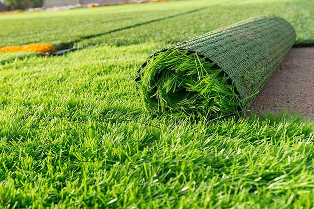 tapete verde sendo enrolado simula quando trocar a grama sintética