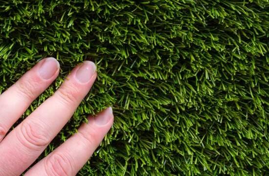 mão encostando no mato e verificando quando trocar a grama sintética